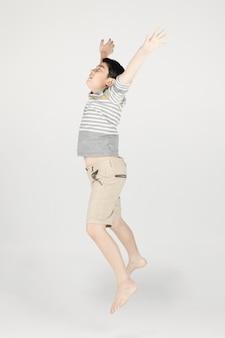 アジアの面白い子少年は灰色の背景にジャンプします。