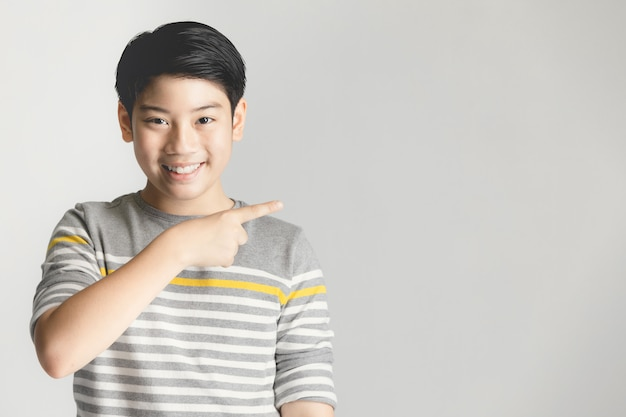 Азиатский подростковый подростка указывает вверх на сером фоне.