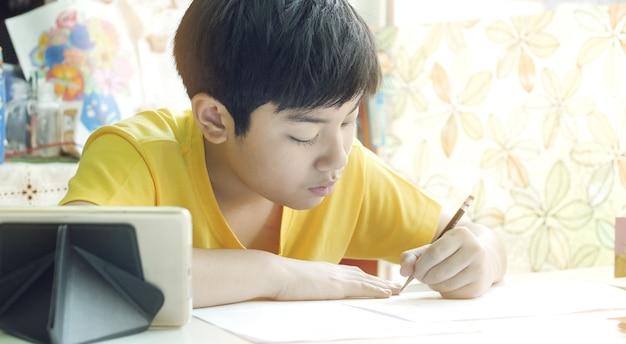 アジアの母は彼女の息子が白いテーブルに宿題をするのを助けます。