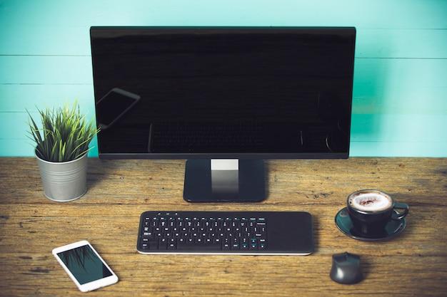 オフィス用品とガジェットを木製テーブルに混ぜる。