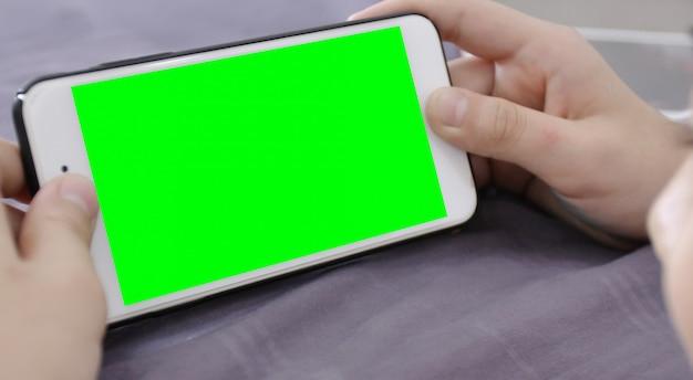 子供は緑色の画面で彼の手に携帯電話を持っています。