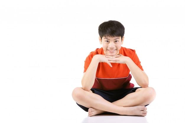 白い背景の上に座っている若いアジア少年の肖像画、