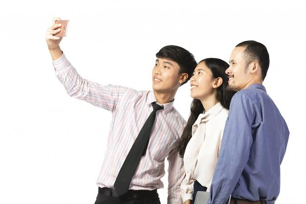 Азиатский работник используя мобильный телефон принимает фото над белизной.