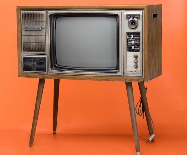 ビンテージテレビはオレンジ色の背景に分離されました。