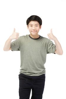 親指をあきらめて緑色のシャツでアジアの興奮している少年。