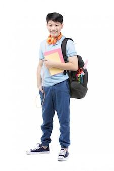 Усмехаясь маленький мальчик студента в голубой футболке поло внутри с книгами и сумкой.