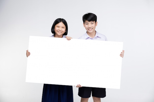 Милые азиатские дети в форме студента с белой доской.