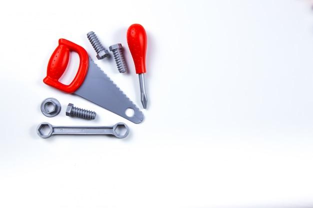 キッズ建設おもちゃツール:カラフルなドライバー、ネジ、木の背景にナット。