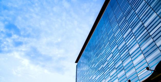 空を反映してモダンなガラスの建物