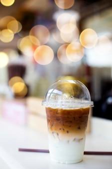 カフェで木製のテーブルの上のプラスチック製のコップで冷たいコーヒー