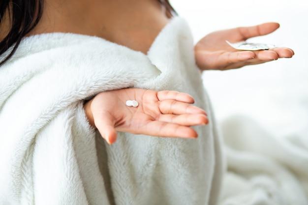 ベッドの上のコンドームと避妊薬を保持しているアジアの女性