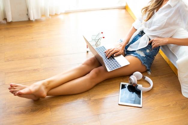 女性のトップビューは、自宅からオンラインショッピングにラップトップコンピューターを使用します。