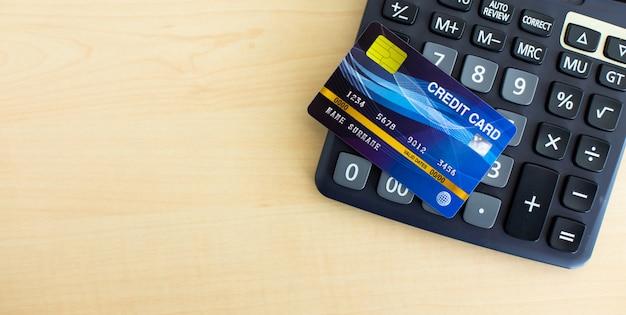 木製テーブルの上の黒い計算機での支払いのためのクレジットカード。