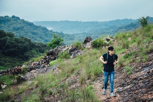 一人で野外を歩いているバックパックを持つ若者ハイキング男。