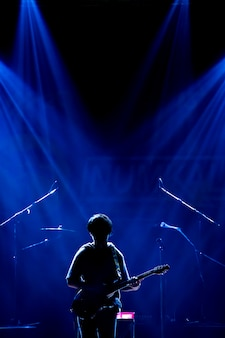 Азиатский музыкант играет на гитаре на черном фоне с прожектором и блики