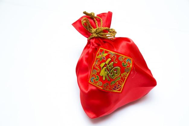 白い背景の上の中国の旧正月のための赤いバッグにお金。