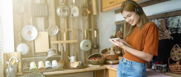 女性は台所でタブレットをプレイしています。