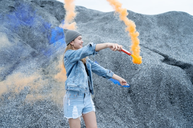 美しい女性彼女はロックグランドキャニオンの場所で花火の煙の色を再生しています。