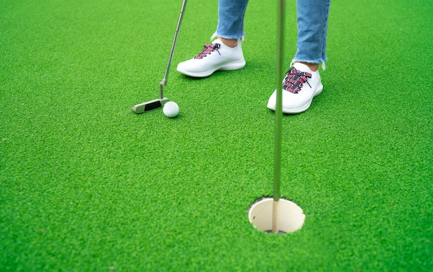 彼女は人工芝でゴルフをしています。