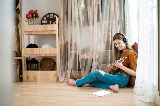 Женщины играют на гитаре в гостиной дома