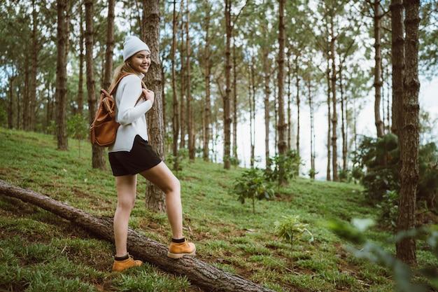 森を歩く白い編みセーターとフードを着ている女性