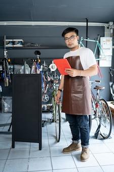 アジア人男性自転車店のオーナー中小企業店内の顧客を歓迎する