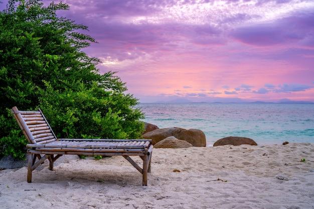 夕暮れ時にビーチの竹の椅子、コピースペース。