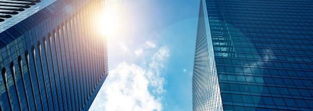 Объектив вспыхивает большой стеклянной офисной башней в городе.