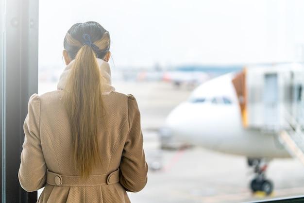 女性は飛行機を待つ、空港でチェックインする時間、コピースペース。