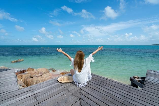女性は海の帽子を身に着け、彼女は幸せで木の橋に座って海辺の海岸を見ます