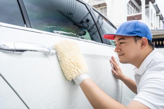 車の詳細、青い制服の男は、手に大きな車を洗うマイクロファイバーを保持して白い車をきれいにする。