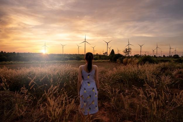 美しい少女は牧草地の上を歩くと彼女は夕暮れの背景に微笑んで風力タービンです。