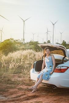 車の後ろに座っている彼女は夕暮れ時に微笑んで美しい少女は風力タービンです。