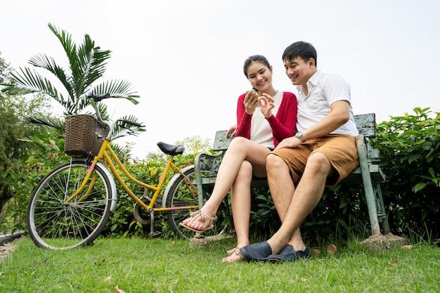 カップルは座っていると自転車公園でスマートフォンを弾きます。