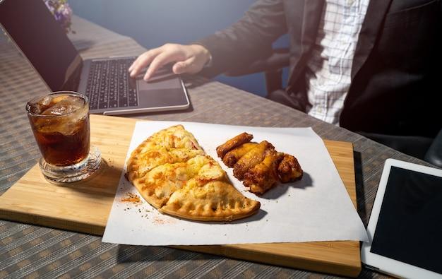 Бизнесмены едят пиццу и куриные ножки барбекю на столе.