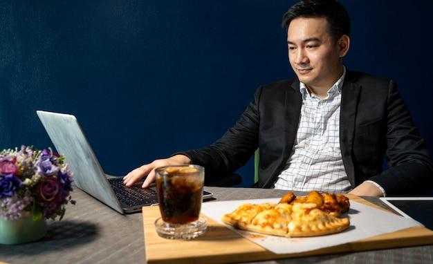 ビジネスマンは、机の上にピザとバーベキューチキンレッグを食べています。