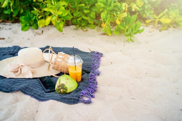 Летняя пляжная сумка с морской шляпкой и солнцезащитные очки на песчаном пляже