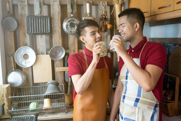 Мужской гомосексуалист лгбт помогает готовить еду на кухне.