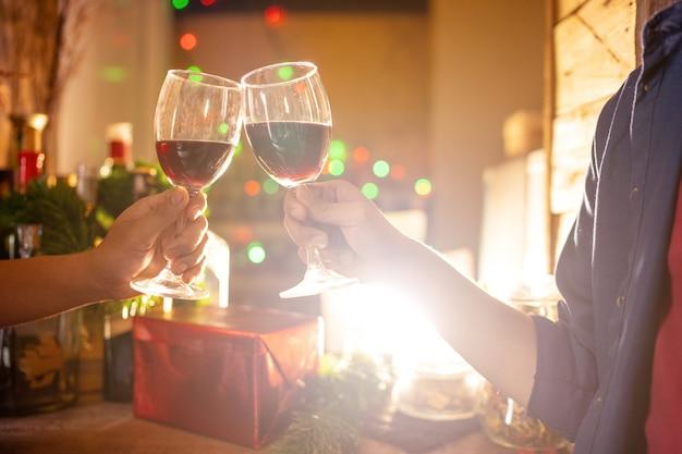 Два человека празднуют, выпивая вино. в рождественский сезон