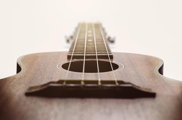 Коричневая гитара укулеле на белом фоне праздник расслабляет время перерыва с музыкой