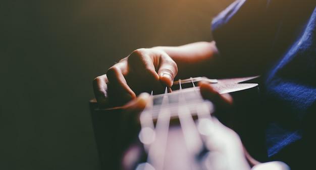 アコースティックウクレレギターを弾く手。音楽スキルを示しています。