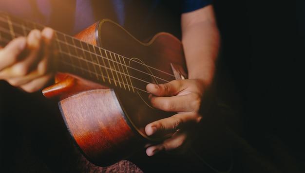 Руки играют на акустической гитаре укулеле. шоу музыкальных навыков