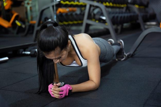 Женщина фитнес-зал женщины, принимая потери веса для тонких и твердых мышц спортсмена