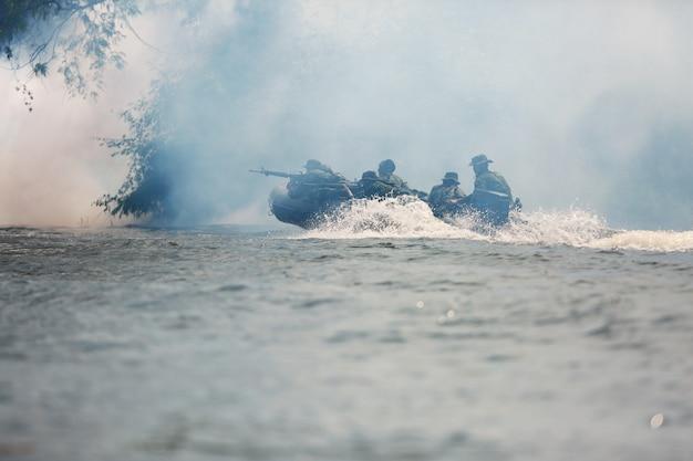 特殊部隊の男性はカモフラージュの制服で軍のカヤックを漕ぐ。