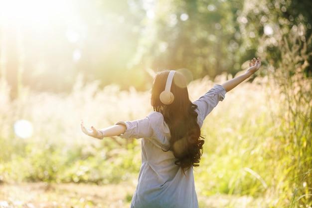 女性は、自然の緑豊かな公園でヘッドフォンで音楽を聴くことによってリラックスし、幸せな女の子。
