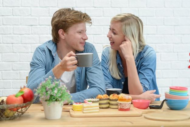 幸せなカップルが白いキッチンでコーヒーブレークとデザートを食べます。