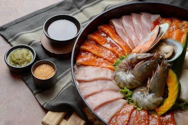 牛肉の側にゴマを添えて、海老の貝をトレイの上に配置してグリル用野菜をテーブルにセット