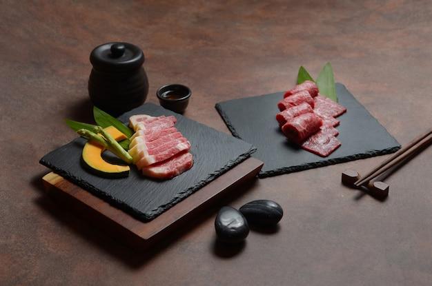 新鮮な生の牛肉のブリスケットスライス、カボチャの部分とアスパラガスの黒い皿岩