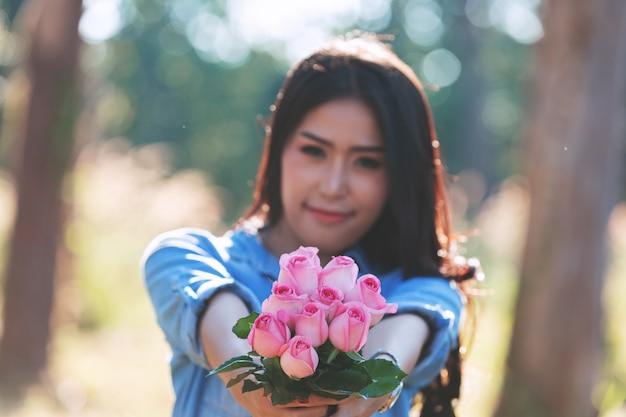 背景のボケ味を持つ庭で花を持って笑顔の遊び心のあるかわいい女の肖像画。
