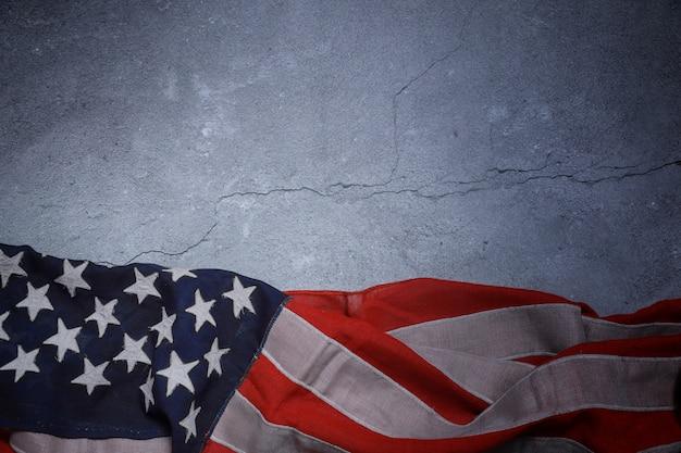 アメリカの国旗がコンクリートの板の上に自由に横になっています。